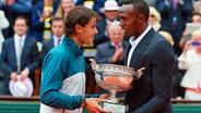 Usain Bolt (r.) überreicht French-Open-Gewinner Rafael Nadal den Pokal. © picture alliance / dpa Fotograf: Anton Denisov