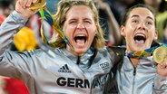 Die Beachvolleyballspielerinnen Laura Ludwig (l.) und Kira Walkenhorst mit ihren olympischen Goldmedaillen. © imago/Conny Kurth