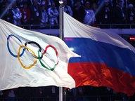 Die olympische und russische Flagge im Stadion von Sotschi © picture alliance / dpa Fotograf: Hannibal Hanschke