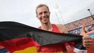 Hochspringer Eike Onnen mit einer Deutschland-Fahne. © DPA Picture Alliance Fotograf: Michael Kappeler
