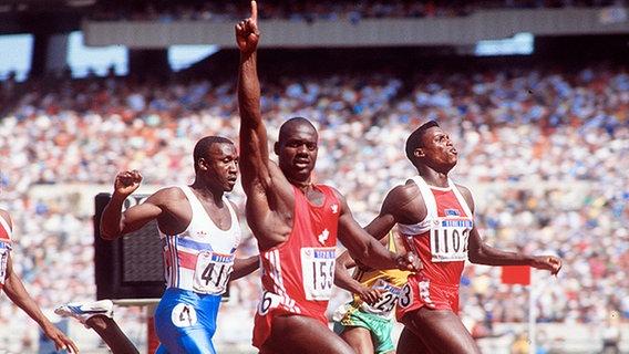 Ben Johnson (M.) jubelt bei den Olympischen Sommerspielen 1988 beim Zieleinlauf des 100-m-Finales. © picture-alliance / Sven Simon