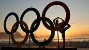 Die Olympischen Ringe am Strand von Rio bei Sonnenaufgang. © dpa bildfunk Fotograf: Yoan Valat